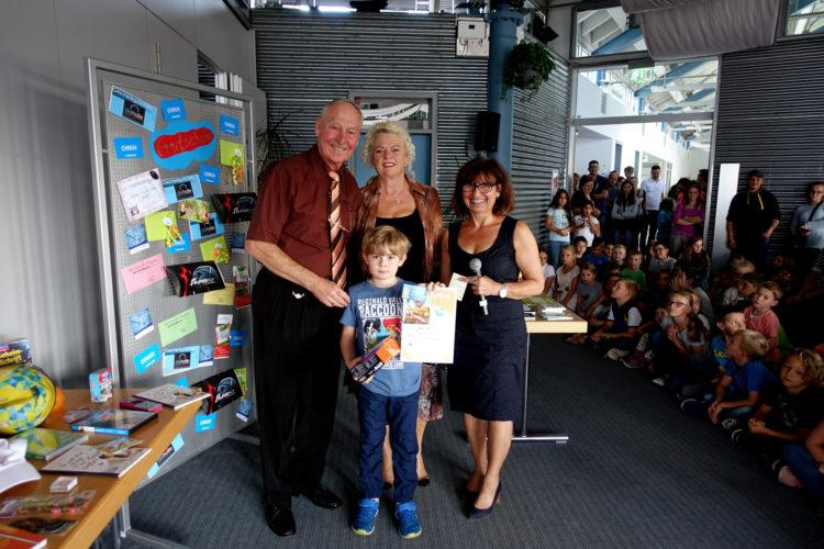 Helmut Klein überreicht im Beisein von Losfee Jutta Klein und der Leiterin der Stadtbücherei Heike Krämer den ersten Preis an Gewinner Ben Palm